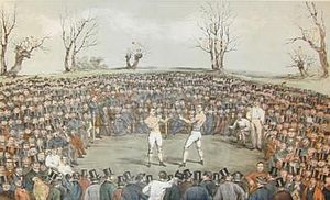 A typical 19th-century boxing match, often held in warehouses, courtyards of inns, or in open fields away from the eyes of local authorities. This painting was by Byrne's friend Jem Ward. | Wikipedia